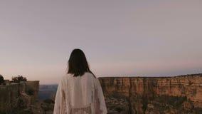 La caméra de mouvement lent suit la jeune femme heureuse marchant vers la vue épique de paysage de montagne de Grand Canyon sur l banque de vidéos
