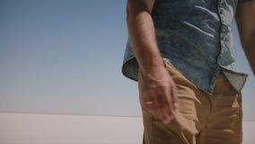 La caméra en gros plan suit le jeune homme décontracté dans des vêtements sport marchant vers la voiture au milieu du désert Utah banque de vidéos