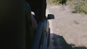 La caméra est du côté du camion de voiture de safari conduisant le long du chemin forestier avec des touristes sur l'excursion de banque de vidéos