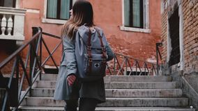 La caméra suit la belle femme de blogger de voyage marchant avec la caméra sur des escaliers dans la rue de Venise, prenant à une clips vidéos
