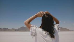 La caméra suit la belle promenade heureuse de femme au milieu du lac chaud ensoleillé de désert de sel de l'Utah, se tournant ver banque de vidéos
