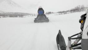 La caméra suit des touristes reposant et montant le bateau de banane de neige banque de vidéos