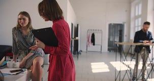 La caméra suit la femme auxiliaire âgée moyenne d'affaires dans la robe rouge entrant dans le grand bureau à la mode de grenier p clips vidéos