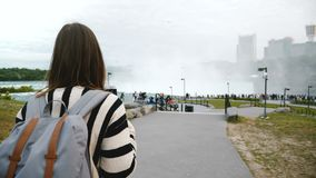 La caméra suit la femme locale réfléchie marchant vers la plate-forme d'observation serrée au mouvement lent de cascade puiss banque de vidéos