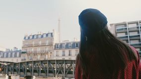 La caméra suit la jeune femme heureuse marchant au balcon ensoleillé de pièce avec la vue de Tour Eiffel, souriant au mouvement l banque de vidéos