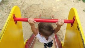 La caméra suit le garçon descendant la glissière des enfants sur le terrain de jeu Enfant heureux jouant sur le terrain de jeu de banque de vidéos