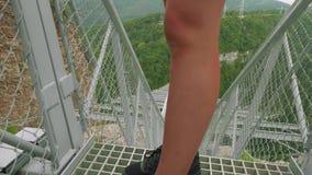 La caméra suit les pieds de la jeune femme sportive caucasienne dans des chaussures sportives marchant sur le pont suspendu en tr banque de vidéos