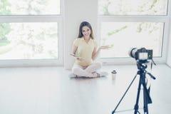 La caméra vidéo enregistre le joli blogger de fille de brune, parlant image libre de droits