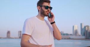 La cam?ra se d?place autour du jeune homme beau pendant qu'il utilise son t?l?phone Portrait Fond brouill? banque de vidéos