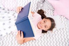 La cama de la endecha del niño de la muchacha leyó la opinión superior del libro Anime los hábitos útiles El niño se prepara para imagen de archivo
