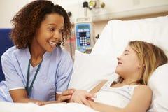 La cama de la muchacha de Sitting By Young de la enfermera en hospital Fotografía de archivo libre de regalías