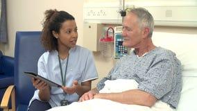 La cama del paciente de Sitting By Male de la enfermera usando la tableta de Digitaces almacen de metraje de vídeo