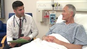 La cama del paciente masculino del doctor Sitting By Senior en hospital almacen de video