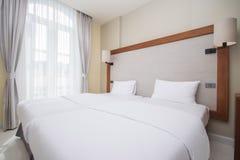 La cama matrimonial en dormitorios se adorna en estilo moderno imagen de archivo libre de regalías