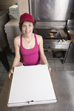La camarera con saca la pizza Foto de archivo libre de regalías