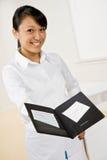 La camarera de sexo femenino ofrece la cuenta Imagen de archivo libre de regalías