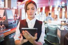 La camarera enfocada que usa la pantalla táctil labra Fotos de archivo