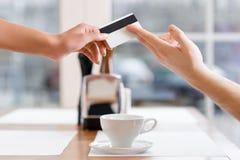 La camarera está tomando la tarjeta de crédito de un cliente Imagenes de archivo