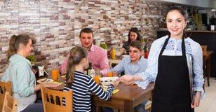 La camarera joven con el menú está invitando Foto de archivo libre de regalías