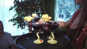 La camarera puso los cócteles de la bandeja en la tabla para las huéspedes en partido en club nocturno celebración holidays almacen de video