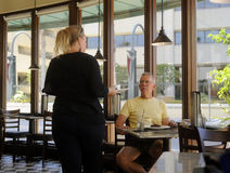 La camarera sirve al cliente Foto de archivo libre de regalías