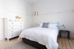 La camera da letto bianca con gli elementi del decoratore in spiaggia ha disegnato i apartmen domestici fotografia stock libera da diritti