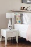 La camera da letto del bambino con i cuscini e la lampada bianchi sul letto moderno Immagine Stock