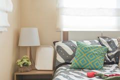 La camera da letto del bambino con i cuscini variopinti sul letto bianco e sulla lampada moderna Immagini Stock