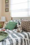 La camera da letto del bambino con i cuscini variopinti sul letto bianco e sulla lampada moderna Fotografia Stock