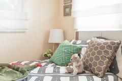 La camera da letto del bambino con i cuscini variopinti sul letto bianco e sulla lampada moderna Immagini Stock Libere da Diritti