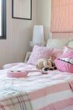 La camera da letto della ragazza nel colore rosa con i cuscini e la bambola immagini stock libere da diritti
