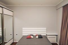 La camera da letto nell'appartamento Letto, guardaroba, comodini nella t Fotografia Stock