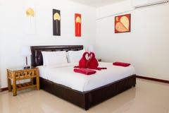 La camera di albergo con letto a due piazze e gli asciugamani gradiscono due cigni immagine stock libera da diritti