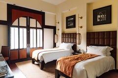 La camera di albergo del letto gemellato con il contemporaneo asiatico decorato, ritiene calda e accogliente a Hanoi, Vietnam immagini stock