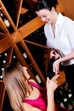 La cameriera di bar offre una bottiglia di vino rosso Immagini Stock Libere da Diritti