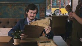 La cameriera di bar porta il menu all'uomo in caffè video d archivio