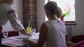 La cameriera di bar porta a signora il suo succo video d archivio