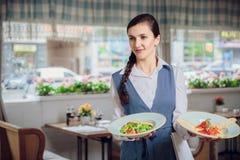 La cameriera di bar sta portando due piatti con i piatti deliziosi restautant Immagini Stock
