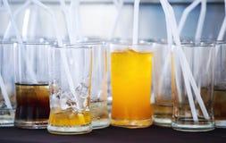 La cameriera di bar tiene il succo d'arancia di vetro sulla tavola Fotografie Stock