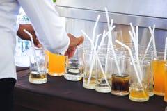 La cameriera di bar tiene il succo d'arancia di vetro sulla tavola Fotografia Stock