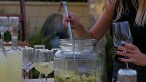 La cameriera di bar versa un vetro di limonata Brocca di limonata stock footage