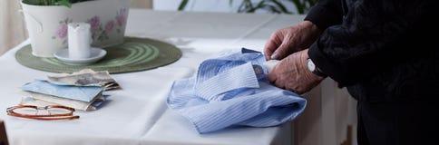 La camicia degli uomini pieganti della donna anziana Immagine Stock