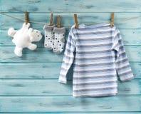 La camicia del neonato, i calzini ed il giocattolo bianco riguardano una corda da bucato immagine stock libera da diritti