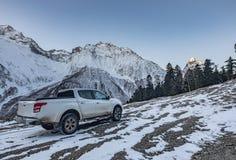 La camioneta pickup está permaneciendo sobre la colina bajo luz del amanecer, Elbrus, Rusia Fotos de archivo