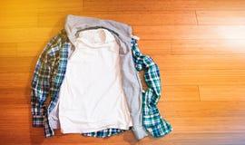 La camisa blanca del inconformista de la camiseta y de la tela escocesa en el piso de madera, imita para arriba, franco Imagen de archivo