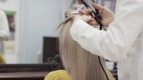 La camisa blanca no identificada de In A del peluquero de la mujer hace el peinado a la muchacha almacen de metraje de vídeo
