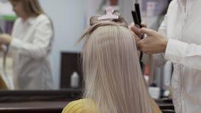 La camisa blanca no identificada de In A del peluquero de la mujer hace el peinado a la muchacha almacen de video