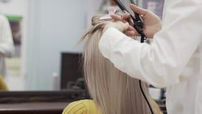 La camisa blanca no identificada de In A del peluquero de la mujer hace el peinado a la muchacha metrajes