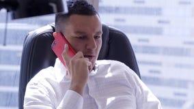 La camisa blanca que lleva del hombre moreno atractivo está hablando en smartphone rojo almacen de video