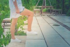 La camisa del desgaste de mujer y la mezclilla blancas del cortocircuito, ella está caminando encima de las escaleras concretas f imagen de archivo libre de regalías